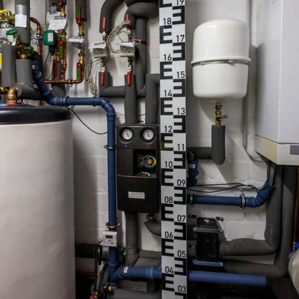 Kellerraum mit Messlatte. Beitragsbild für einen Beitrag über Hochwasserschutz und Schwachstellen im Haus, die bei Rückstau Wasser in den Keller lassen können.