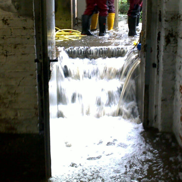 Bild einer Überschwemmung: Wassermassen dringen durch einen Kellereingang in das Gebäude