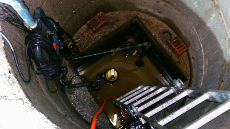 Verschmutzter Schacht mit Drainagepumpe