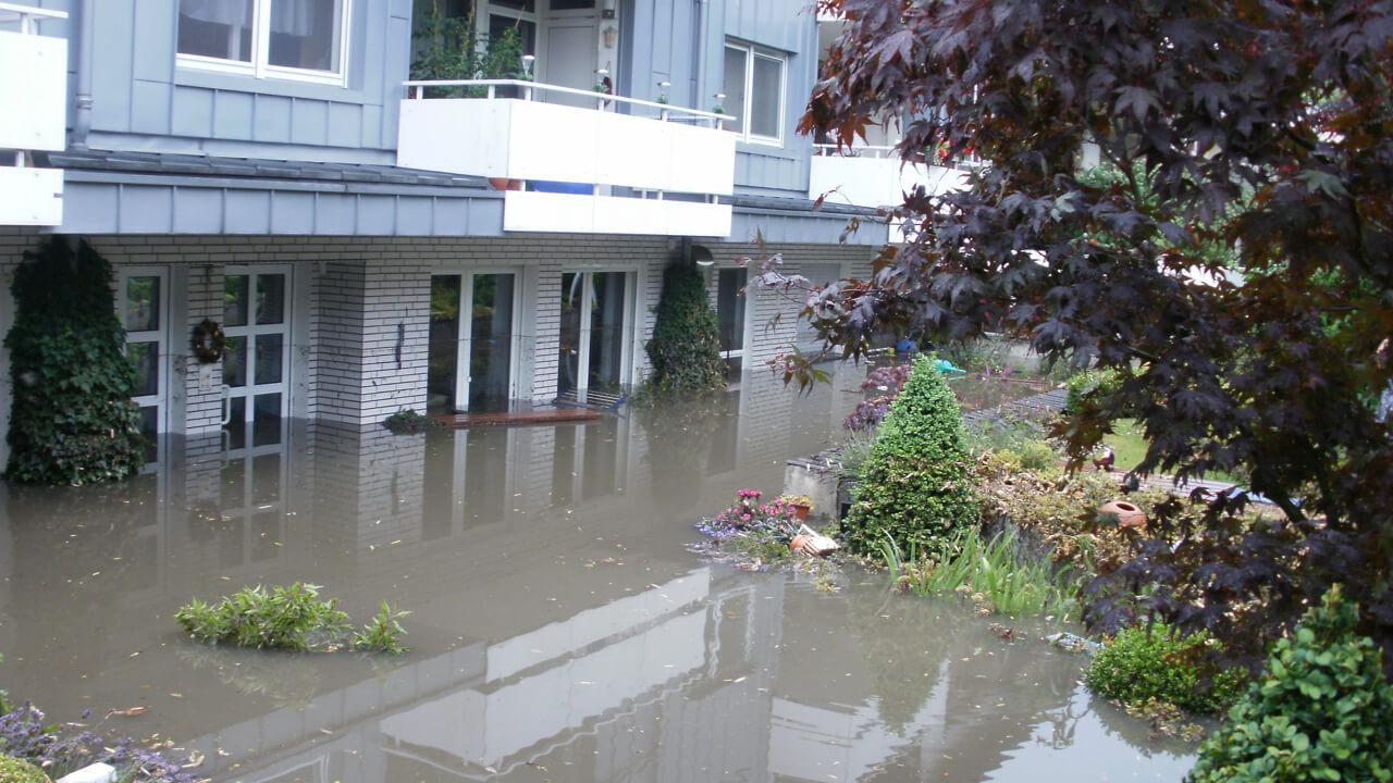 Überschwemmung in einem Wohngebiet: Das Wasser steht bis zu den Türklinken im Erdgeschoss