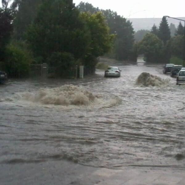 Bild einer Überschwemmung: Aus dem überlasteten öffentlichen Kanalnetz dringen Wassermassen und überfluten die Straße. Starkregen und Extremwetter werden in Zukunft verstärkt zu Rückstau und überfluteten Kelleranlagen führen.