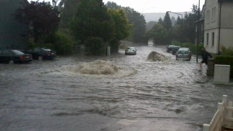 Bild einer Überschwemmung: Aus dem überlasteten öffentlichen Kanalnetz dringen Wassermassen und überfluten die Straße