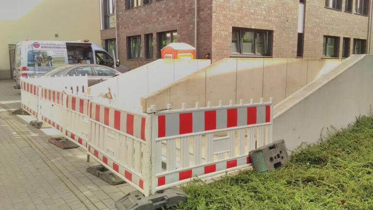 Garageneinfahrt mit Absperrungen, Rückstauprofi-Montageauto im Hintergrund