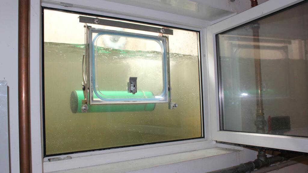 Vollautomatisches Hochwasserfenster während einer Testflutung: Das Fenster hat geschlossen, bevor das Wasser die Fensterunterkante erreichen konnte